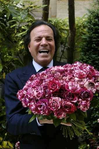 Le chanteur espagnol Julio Iglesias pose avec un bouquet de roses à son nom, lors d'une présentation de la variété à la presse, le 28 juin 2007 à Paris.   Spanish singer Julio Iglesias poses with roses bearing his name, during a presentation to the press 28 June 2007 in Paris.  / AFP PHOTO / STEPHANE DE SAKUTIN