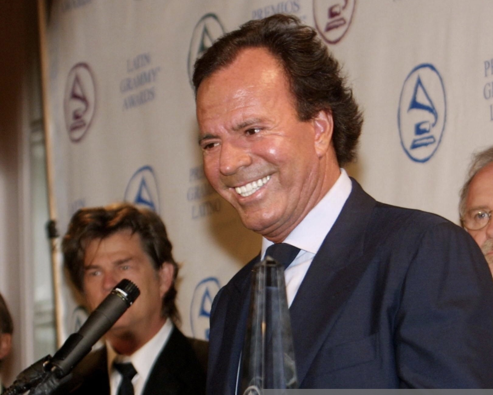 BEVERLY HILLS, UNITED STATES: Spanish singer Julio Iglesias (C) speaks to the the media as he holds the Latin Academy of Recording Arts and Sciences Person of the Year Award, presented to him prior to a gala tribute dinner 10 September, 2001 in Beverly Hills, CA. The Latin Grammys will be presented 11 September. AFP PHOTO/LEE CELANO (Photo credit should read LEE CELANO/AFP via Getty Images)